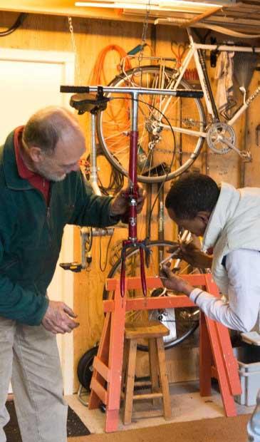 in zijn tot werkplaats omgebouwde garage repareert Dik van de Meent de fietsen, daarbij geholpen door Mehari Brhane uit Eritrea aan wie hij het fietsenmakervak leert