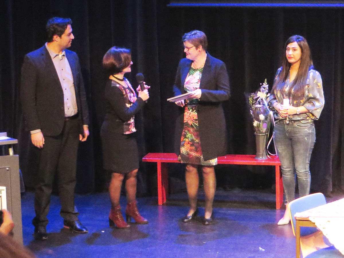 Saber Alizai, Nariné Khenkikian en Parisa Rostami bij de uitreiking van het jubileumboek aan wethouder Anne Brommersma tijdens de zilveren Jubileum viering van Steunpunt Vluchtelingen De Bilt
