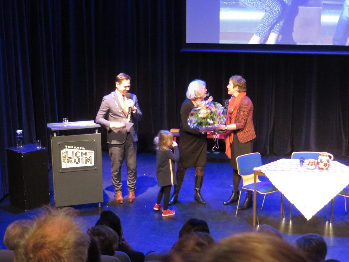 Gerda Terlingen krijgt felicitaties en bloemen nadat ze van burgemeester Sjoerd Potters de Chapeaupenning van de gemeente De Bilt ontvangen heeft tijdens de zilveren jubileum viering van Steunpunt Vluchtelingen De Bilt