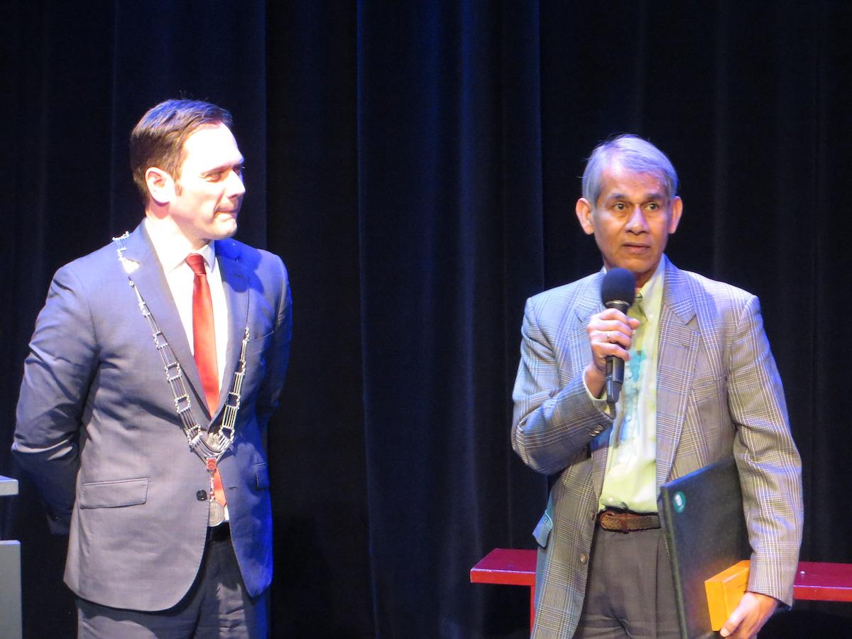 Roy Chowdhury krijft de Medaille van Verdienste uitgereikt door burgemeester Sjoerd Potters tijdens de zilveren jubileum viering van Steunpunt Vluchtelingen De Bilt