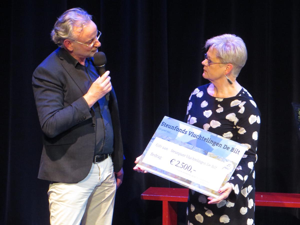 Steunpunt Coördinator Hanneke Eilers ontvangt een gift van Hinnejan Elswijk, voorzitter van het Steunfonds Vluchtelingen De Bilt tijdens het zilveren jubileum viering van Steunpunt Vluchtelingen De Bilt
